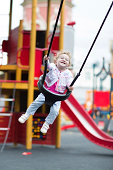 Happy laughing baby girl in a swing on a playground