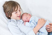 Happy laughing boy holding his sleeping newborn baby brother