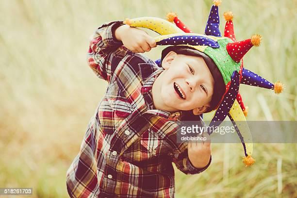 Glücklich Lachen Junge spielt & mit Joker Hut im Freien