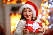 happy laughing child girl with christmas present at home