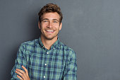 Young handsome man leaning against grey wall with arms crossed. Cheerful man laughing and looking at camera with a big grin. Portrait of a happy young man standing with crossed arms over grey backgrou