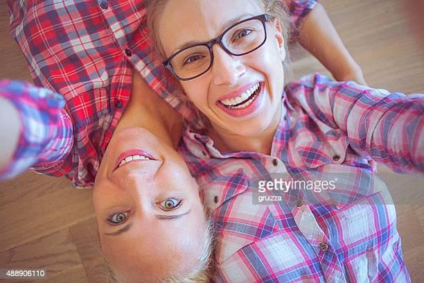 couple heureux et lesbiens à la maison prenant une autophoto photos sur smartphone