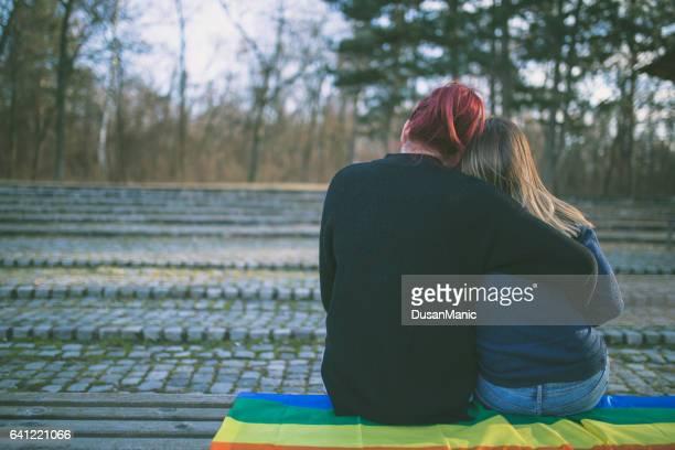 Couple de lesbiennes heureux assis sur le banc dans le parc