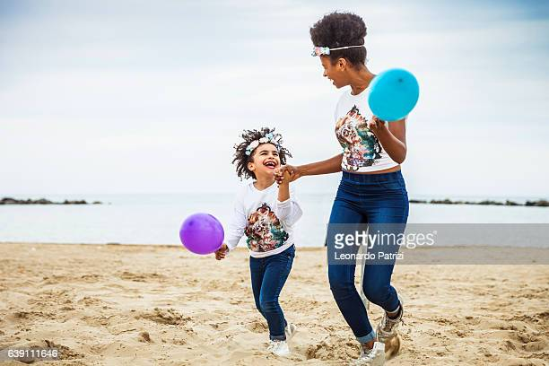 Happy lifestyle, sister together playing on the beach