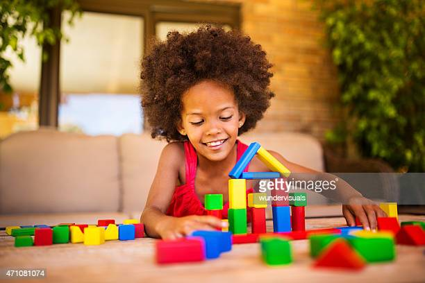 Happy little Afro girl palying with colourful building blocks