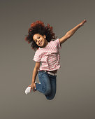 Beautiful little african-american girl jumping a gray studio background, copy space. Studio shot of cute happy child