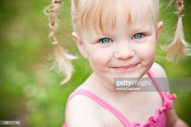 Felice piccolo ragazza bionda sorridente all'esterno