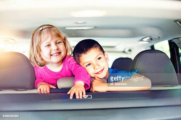 Happy little boy and toddler girl travel by car.