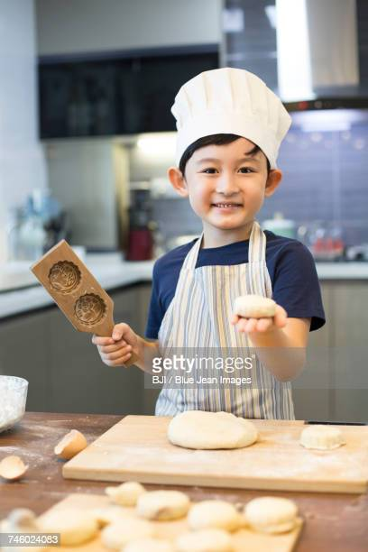 Happy little boy baking at home