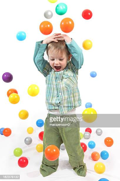 Happy little boy being rained on by colored balls