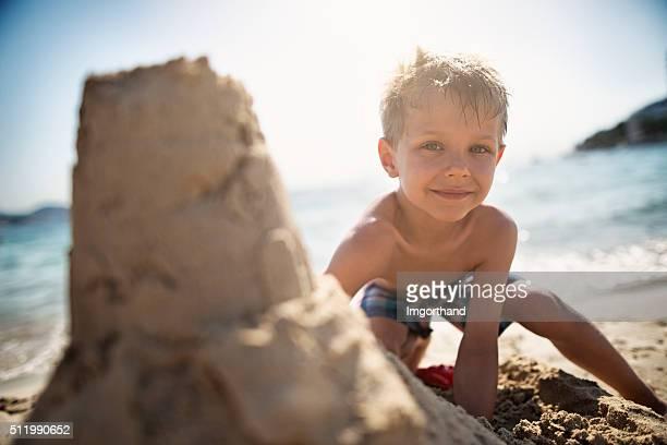 Happy little boy building a sandcastle on a beach