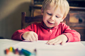 Happy little boy drawing a picture
