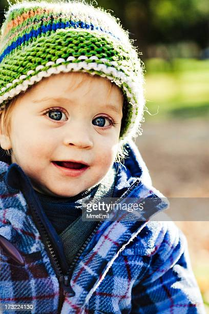 Happy little boy dressed in plaid shirt and green knit hat
