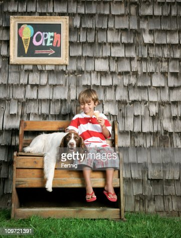 Happy little boy eating ice cream with his dog : Stock Photo