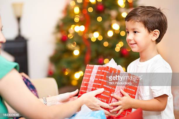 Happy Little Boy Giving Present To Mother on Christmas Morning