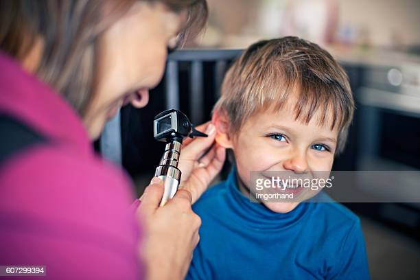 Happy little boy having home visit ear exam