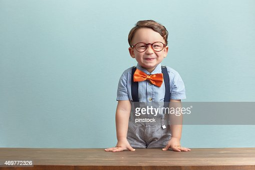 Happy little boy in an orange bow tie and glasses