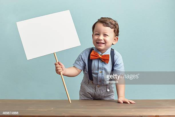 Happy little boy is holding a banner.