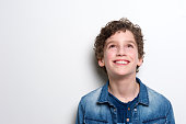 Close up portrait of a happy little boy looking up on white background