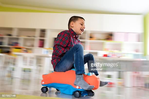 Glücklich kleiner Junge auf einem Spielzeug-Reiten in Bewegungsunschärfe.