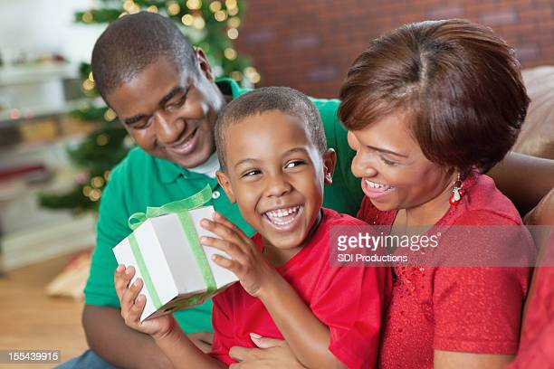 Happy little boy opening Christmas present with parents