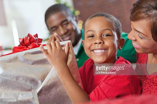 Heureux petit garçon ouverture cadeau de Noël avec leurs parents