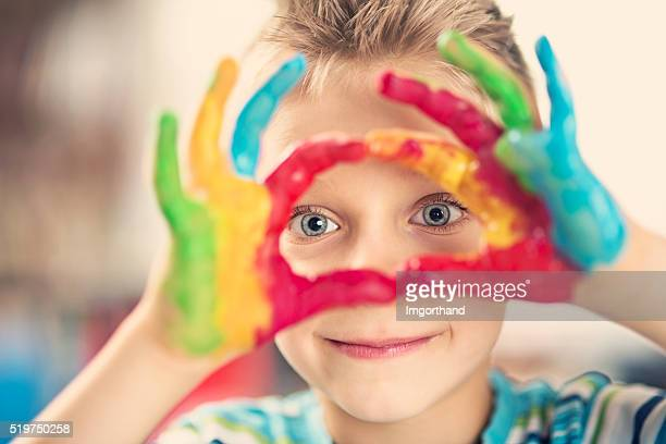Happy little boy painting with hands