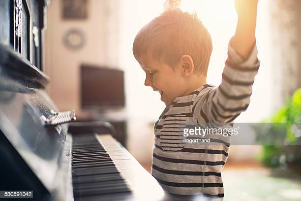 Happy little boy practicing piano