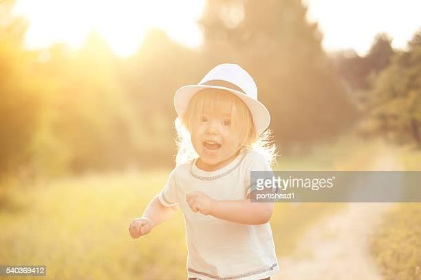 Happy little boy running in a park