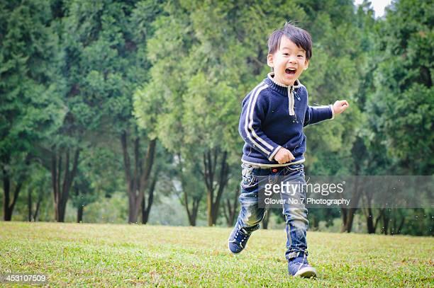 Happy little boy running on the grass.