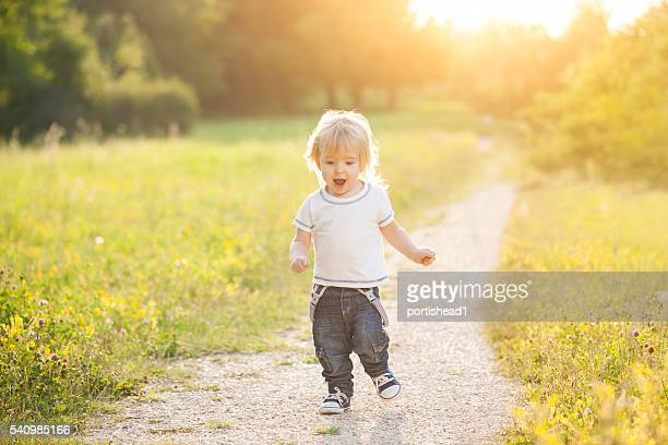 Happy little boy running outside