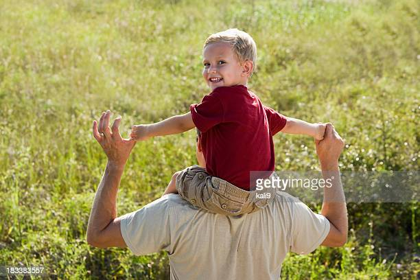 Heureux petit garçon assis sur les épaules du père haut
