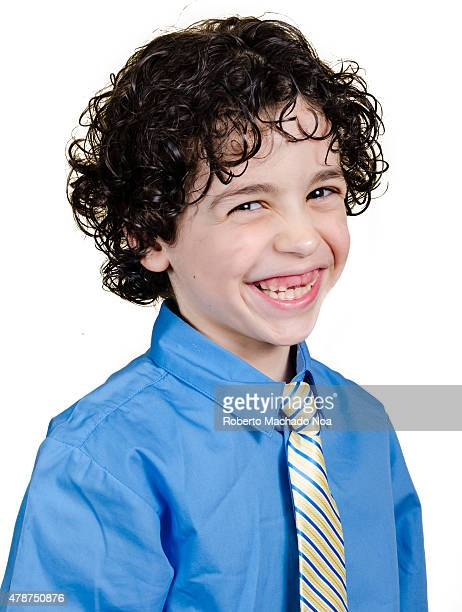 Happy little boy smiling in a blue shirt and tie over white background