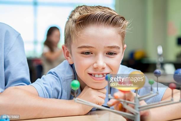 Happy little boy studying solar system model in classroom