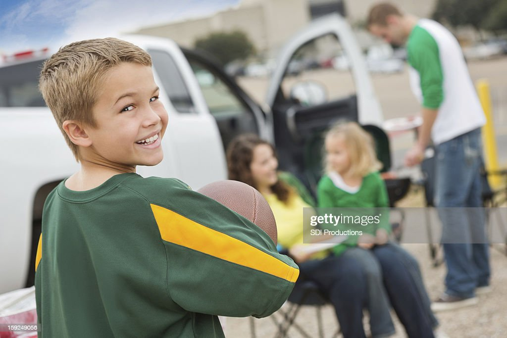 Happy little boy tailgating with family near college football stadium : Stock Photo