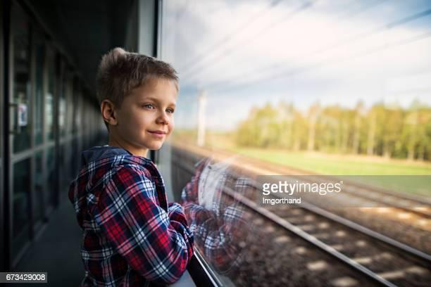 Happy little boy travelling on train