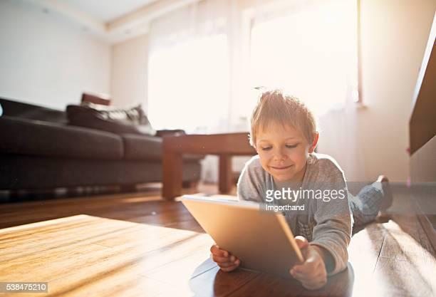 Glücklich kleiner Junge mit modernen tablette auf dem Boden