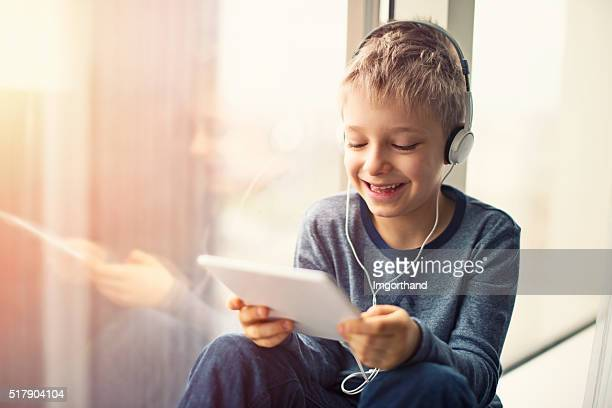 Happy little boy using tablet with headphones