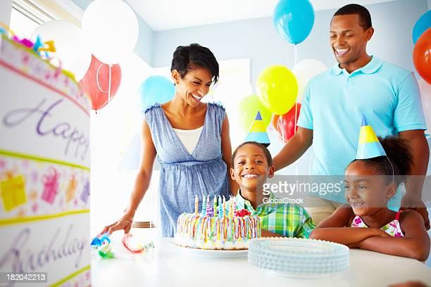 Heureux petit garçon avec sa famille célébrer un anniversaire