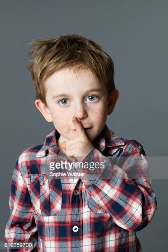 happy little child keeping mystery with his finger on lips : Foto de stock