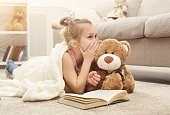 Cute happy little casual girl embracing teddy bear, reading book and sharing secrets with her favorite toy friend. Pretty kid at home, lying on the floor near sofa