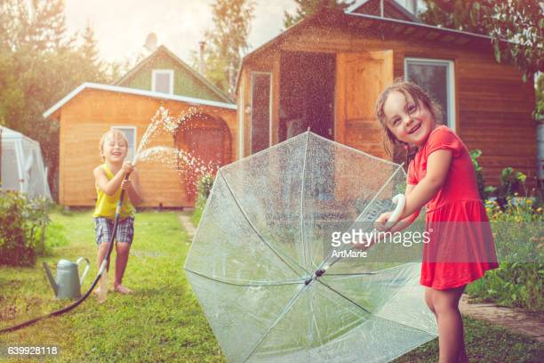 Happy little girl and boy playing with garden sprinkler