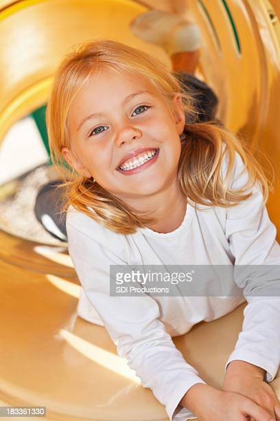 Happy Little Girl at top of playground slide tube