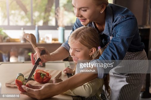 Happy little girl cutting a peper with her mother : Stock Photo