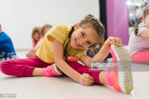 Happy little girl doing stretching exercises in a health club.