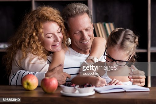 Happy little girl drawing with her grandparents : Stock Photo