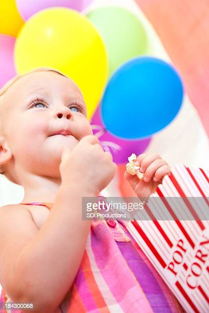 Happy Little Girl Eating Popcorn Inside a Circus Tent