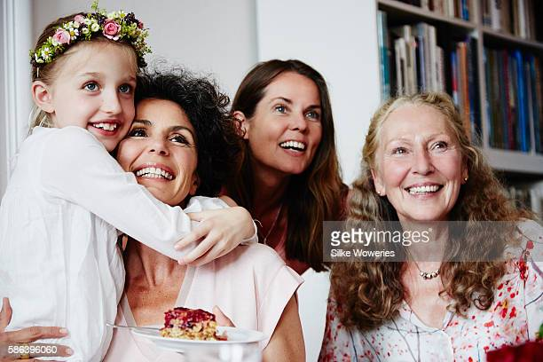 happy little girl embracing her mother wearing a floral wreath