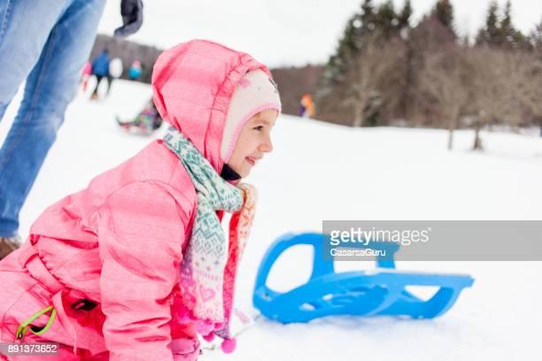 Glückliche kleine Mädchen, die Spaß auf der Piste nach einem Sturz aus dem Schlitten