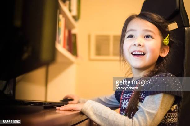 Happy little girl having fun using a computer at home